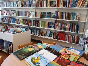 bokhyller langs vegg, bord med bøker